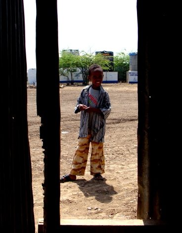 A young boy waits in the Reception Center at the Kakuma Camp.